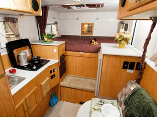 Oregon expandable truck camper interior showing kitchen, seating and